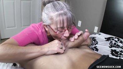 Стройная седая бабка в очках отсасывает хуй молодого чувака на кровати