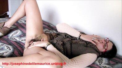 Очкастая баба показывает черную волосатую пизду прилюдно и мастурбирует на кровати