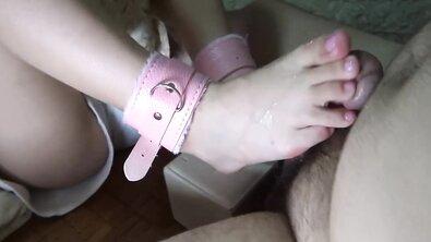 Азиатка в розовых кандалах на щиколотках дрочит ногами хуй